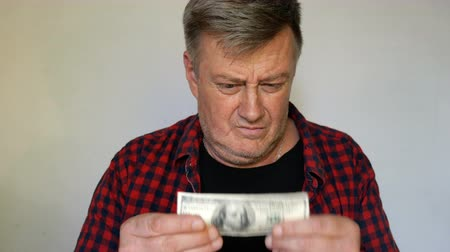 különc : Eccentric senior man with gray hair holds a banknote of one hundred US dollars in his hands and is madly happy about it. Close-up portrait. On light background.