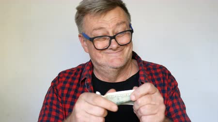 szörnyszülött : Eccentric senior man with gray hair holds a banknote of one hundred US dollars in his hands and is madly happy about it. Close-up portrait. On light background.