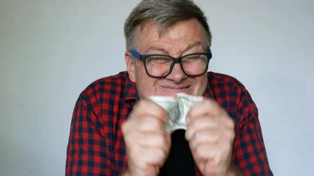 урод : Eccentric senior man with gray hair holds a banknote of one hundred US dollars in his hands and is madly happy about it. Close-up portrait. On light background.