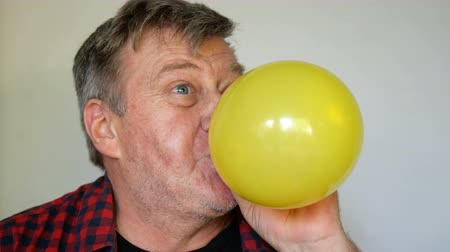 výstřední : Eccentric senior man, with gray Hair inflates a ball, then pierced and bursts it and screams loudly, opening his toothless mouth wide. Close-up portrait. On light background. Dostupné videozáznamy