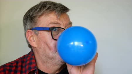 unbalanced : Eccentric senior man, with gray Hair inflates a ball, then pierced and bursts it and screams loudly, opening his toothless mouth wide. Close-up portrait. On light background. Stock Footage