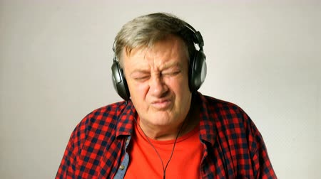 one by one : Expressive adult senior man, listens to music on his headphones, sings along and moves to beat of music. On light gray background. Close-up. Outdoors.
