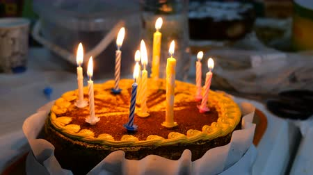 gyertyák : Beautiful delicious birthday cake with burning candles is on kitchen table. Maybe it was prepared for birthday celebration. Selective focus. Close-up. Stock mozgókép
