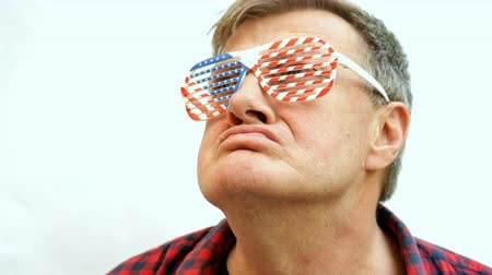 fidelity : Serious senior mature man puts on decorative glasses in the colors of the American flag and proudly raises his head. Concept of patriotism and loyalty to America. Close-up. Stock Footage