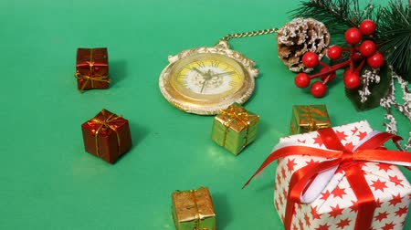 önemsiz şey : Christmas decorations, holiday decor, pine branch, pine cone, berries. Human hands lay a Christmas tree toy. New years clock. Falling down many gifts. Green background. Copy space. Close-up. Stok Video