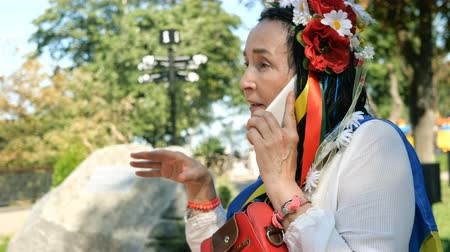 Elegant senior woman, in white dress and with wreath with flowers on her head, speaks emotionally on her phone in outdoors park. Portrait.