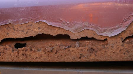 Part of an old rusted piece of metal, possibly a car hood with rust, holes and peeling paint.
