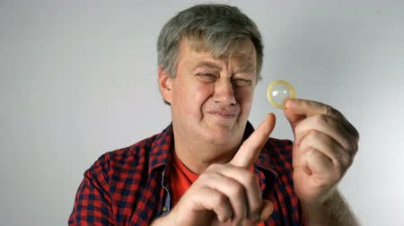 Senior man holding and point at condom in his hands, and smiles with lust, looking at camera. Concept of active sex life at elderly age. Stock mozgókép