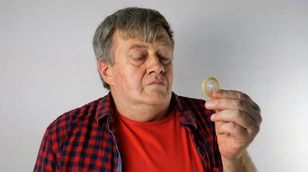 Senior man with gray hair in casual clothes looks at condom with disappointment and sadness, sighs and shrugs. Concept of sexual problems and impotence at elderly age.