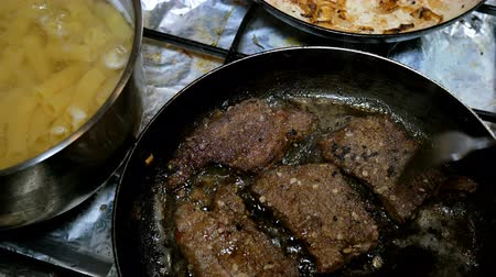 candida : Homemade cooking. Boiled pasta pipe and beef liver or meat steaks is prepared on kitchen stove on home or restaurant kitchen. Close-up.