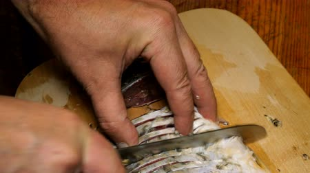 čištěný : Homemade kitchen. River fish carp, is cutting into pieces, with kitchen knife for subsequent frying, on cutting board on kitchen table. Close-up.