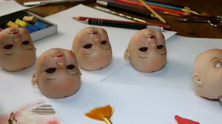 instrument maker : Making dolls. Master painter carefully paints lips of blank for doll with thin brush. Concept of combining work and hobbies.