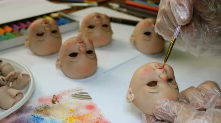 marionet : Making dolls. Master painter carefully paints lips of blank for doll with thin brush. Concept of combining work and hobbies.