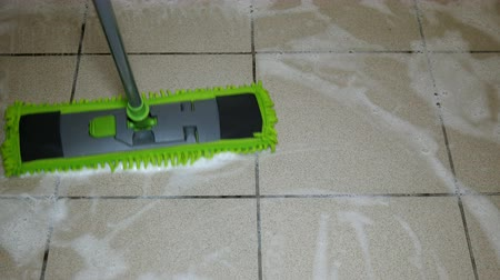 zametání : Domestic life. Tiled Floor cleaning used modern flat mop and cleanser with foam. Concept of housework. Close-up. Dostupné videozáznamy