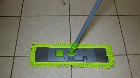mopping : Domestic life. Tiled Floor cleaning used modern flat mop with a convenient rotating handle. Concept of housework. Close-up.