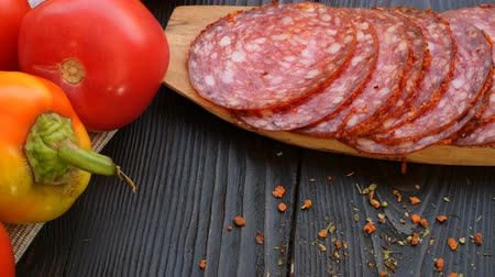 capsicum : Homemade kitchen. Making sandwich. Sliced salami and ripe vegetables lie on dark wooden table. For the preparation of sandwich with sausage. Motion camera. Stock Footage