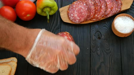groene pepers : Homemade kitchen. Human hands preparing sandwich of chopped salami and tomato. Concept of making fast food.