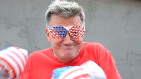 символы : Funny people. Crazy senior man shows or simulates punches, with glasses and boxing gloves in colors of American flag. And at the end shows a gesture of victory. Close-up.