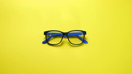wzrok : Human hands search, find and take eye glasses in blue plastic frame. On yellow background.