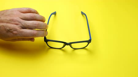 nearsightedness : Human hands search, find and take eye glasses in blue plastic frame. On yellow background.