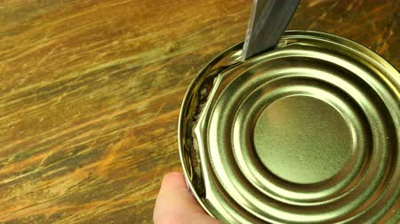 enlatamento : Canned meat. Human hands open canned stew in tin can, by dint of kitchen knife on a wooden table. Close-up.
