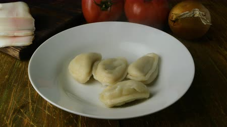 pierogi : Fresh boiled homemade dumplings or vareniki with stuffing. With hot steams. Impose in white plate. Served with fried onion and lard. Ukrainian and russian national cuisine. Close-up.