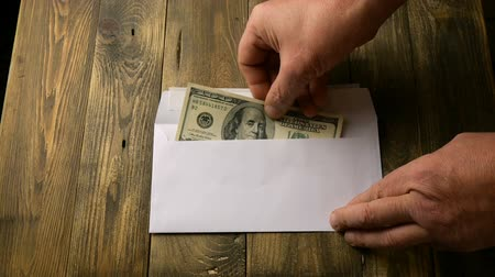donate : Human hands put two one hundred dollar bills in cash into white paper envelope that lies on brown wooden table. Concept of saving money or corruption and shadow economy. Slow motion.