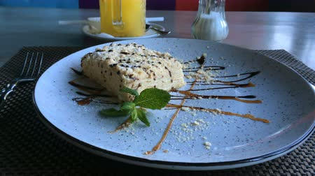 Tasty dessert. Slice of Napoleon cream cake, made from puff pastry, lies on a plate on a table in a restaurant or cafe.