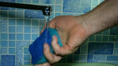 Human hand washes and rinses washcloth for washing dishes under running water from water tap in bathroom or in kitchen. Homework concept. Close-up.