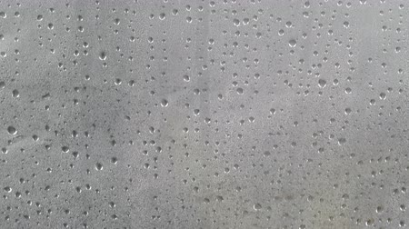 Many water drops on dark gray surface condensation. Abstract background texture.