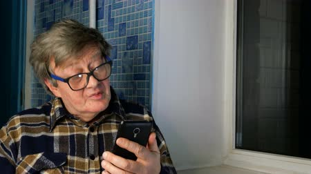 Funny senior adult man in casual clothing is sitting by window and emotionally talking on video call with someone dear to him, from his smartphone. Close-up. Stock mozgókép