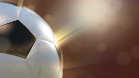 soccer ball slowly flying through the water drops emitting rays of light, 4k 3d animation