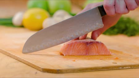 cutting up : Close-up of knife cutting salmon fish on fillets with knife