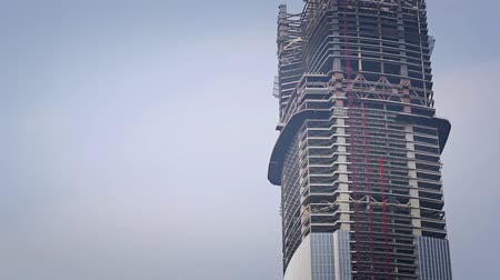 skyscraper : The plane flies behind a skyscraper under construction Stock Footage