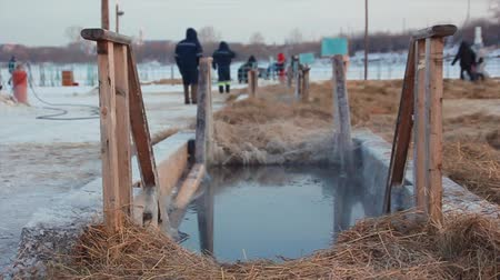 baptismal : The  man bathes in an ice-hole on the Epiphany in Russia Stock Footage