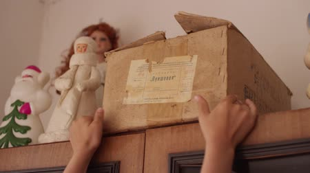 poškozené : Childs hands pulls the old box from the top of closet Dostupné videozáznamy