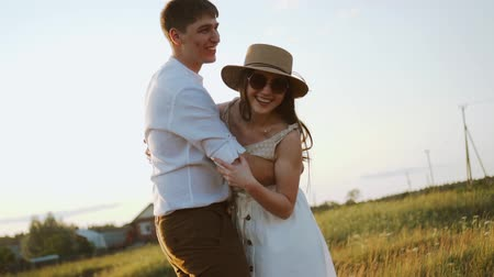 casado : happy millennials couple play and have fun at sunset, enjoying and laughing, smiling. Girl wears hat, rural couple. Portrait of loving married partners walking outdoors. Slow motion