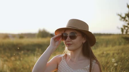 Portrait of pretty caucasian girl in hat is putting on sunglasses and smiling. Rural landscape at sunset and stylish young woman model posing. Summer evening