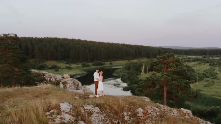 Young couple hugging on the edge of cliff, flying around aerial shot. Romantic scene outdoors near river on the rock with lonely tree. Stock mozgókép
