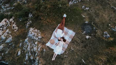 Lovers couple laying on the edge of rock cliff. Romantic picnic outdoors. Couple on a plaid on the mountain. Casual style clothes. Amazing aerial view of rocks in summer. Concept of millennials relaxing