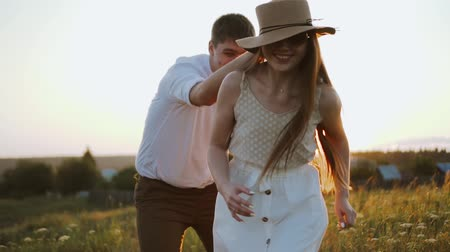 Millennials stylish couple have fun playing with hat, running and catching each other. They enjoy sunset outdoors, walking together in beautiful meadow. Careless and happy boyfriend and girlfriend