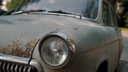 арматура : Front of abandoned retro car with peeling paint. Headlights of old rusty vintage auto, close up. Slow panning from headlights to windshield. Corroded chrome fittings.