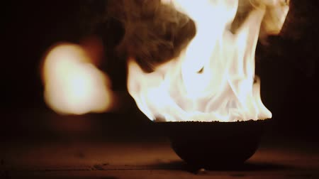 poz : Flames in fire bowl in dark background, metallic bowls on ground, ritual burning in bowls at night. Slow motion.