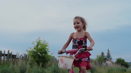 tongue out : Cute little girl riding bicycle in countryside. Funny child of european appearance wearing a red dress is riding bike. She happy, smiles and sticks out tongue. Slow motion.