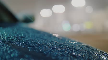 sneeuwbal : Rain with snow falls on blue azure hood of car, raindrops dripping on surface of hood. Night city blurred bokeh background. Macro view, slow motion.