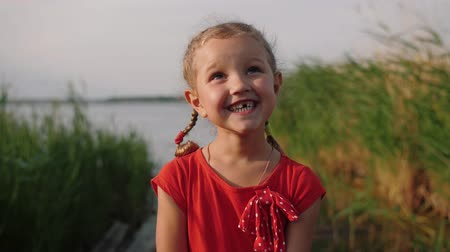 косички : Portrait of caucasian cute little girl with pigtails and pretty face looks at camera and smiles in background of lake and thicket of reeds and grass. Child dressed in a red dress laughing, close up