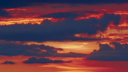 distante : Dramatic evening clouds floating in fire sky, epic orange sunset. Blue clouds moving in background of fire sunset, colorful timelaps. Stock Footage