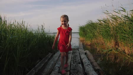 Caucasian cute little girl in a red dress walk on old wooden pier between thicket of reeds near lake. Happy young child walking by the lake and smiling. Childhood, freedom.