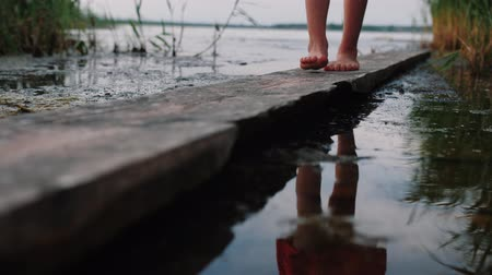 Little girl feet walk along old wooden board by the lake, her reflection flickers in the water. Close up, slow motion.