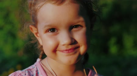 Close up of happy cute little girl of european appearance with brown eyes looking at camera and smiling in park on background of greenery or vegetation.
